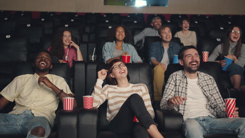Slow motion of happy millennials laughing in cinema watching interesting film Footage