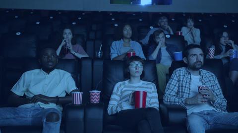 Slow motion of emotional people watching scary movie in cinema closing eyes Footage