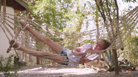 Relaxing girl swinging in hammock at summer vacation. Teenager girl relaxing in Live Action
