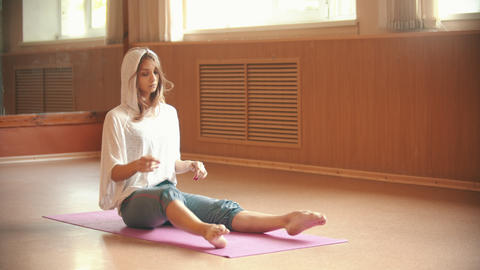Young slim woman sitting on the yoga mat and puts her legs in lotus position Footage