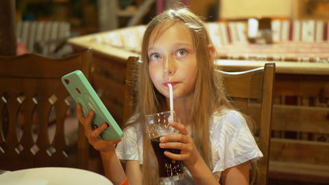 Teenager girl drinking from glass fizzy water and looking smartphone. Young girl Live Action