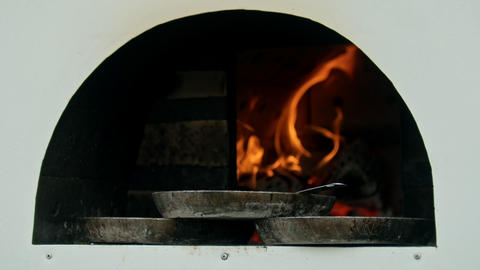 A lighted and heated oven with fire inside - three pans standing on the edge of Live Action