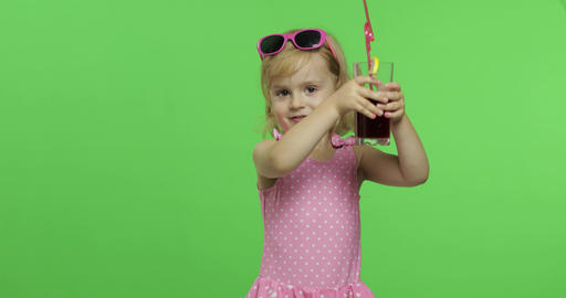Child in pink swimsuit drinks juice cocktail with drinking straw. Chroma Key Live Action