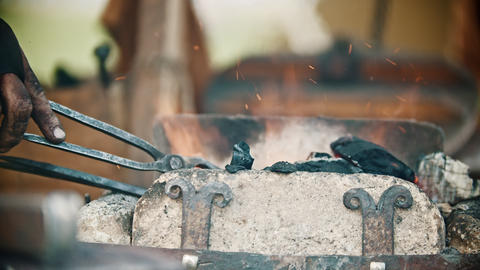 Blacksmith working with an iron details in his workshop - heating up the detail Live Action