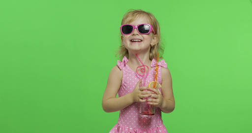 Child in pink swimsuit drinks juice cocktail with drinking straw. Chroma Key Footage