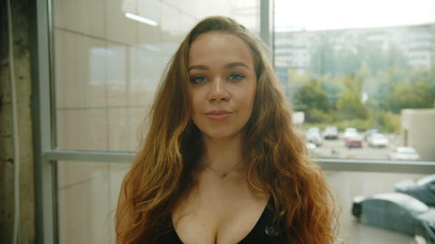 A woman with curly hair in sports bra looking in the camera Footage