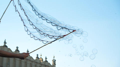 Many multicolored soap bubbles flying over a historic square in Krakow in summer Footage