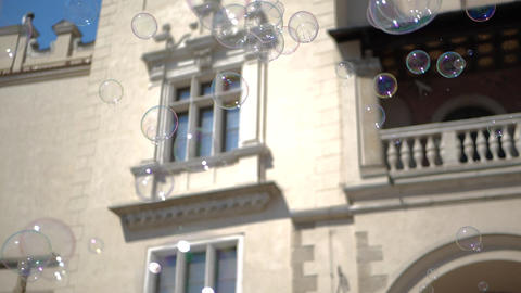 Multishaped soap bubbles are flying at historic house in Krakow square in summer Footage