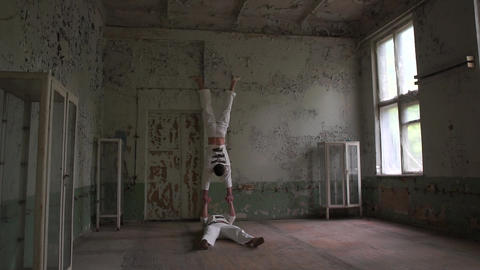 One psycho man man doing handstand and the second turns and lies in slo-mo Footage