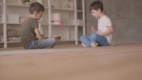 Two brothers sitting on the floor playing with the toy car sitting on the floor Live Action