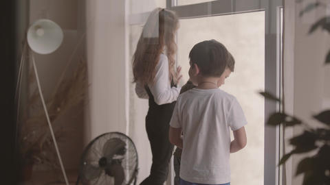 Children look out of the wide window from home. Older sister playing at home Live Action