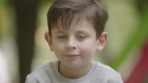 Portrait of cute smiling boy looking at the camera sitting outdoors. Carefree Footage