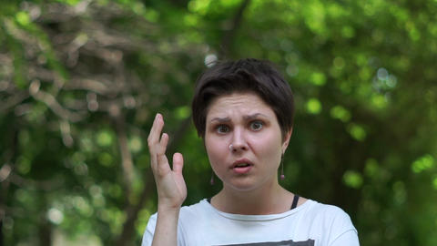 Very shocked brunette woman standing and raising her hand in a wood in slo-mo Footage