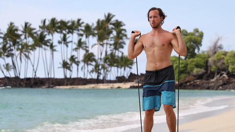Resistance band Exercises - Man with fitness elastic band exercising on beach Live Action