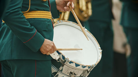 A wind instrument military parade - a person in green costume playing drums Live Action