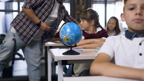 Male teacher of elementary school walking between desks puts computers tablet on Live Action