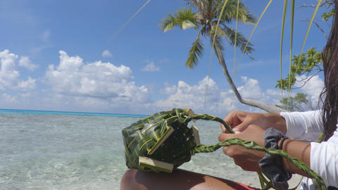 French polynesian culture - woman weaving a purse out of palm leaves Footage