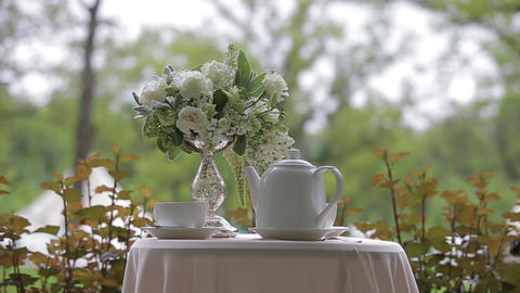 Hot tea in white cups and white teapot served outdoors on a white table Live Action