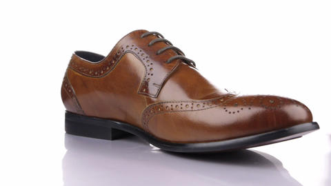 Rotation of a stylish classic brown shoe with laces on a white background Live Action