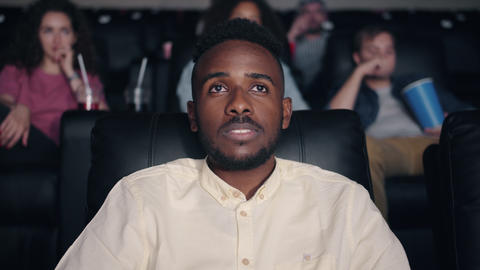 Shocked African American man watching film in cinema with open mouth Live Action