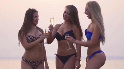 Young girls drinking champagne on the seashore. Celebrating happy start of their Footage