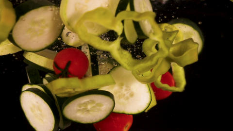 Fresh cut vegetables fall in water. Slow motion of fresh and organic vegetables fall in water Footage