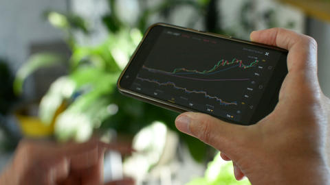 Businessman is checking Bitcoin price chart on crypto exchange on amobile phone Footage