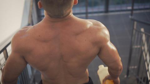 Bodybuilder walks downstairs Footage