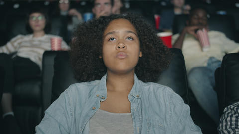 Sad African American girl watching drama in cinema with sadness and compassion Footage