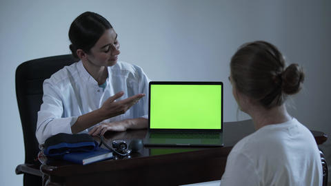 Professional female doctor tells something to female patient and showing with Footage