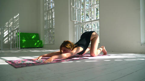 Flexible young red-haired healthy caucasian woman practicing yoga on the mat in Footage