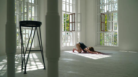 Young red-haired healthy caucasian woman practicing yoga on the mat in the white Footage