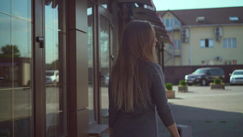 Cute girl walks in an urban environment. A happy girl in a gray dress has fun Footage