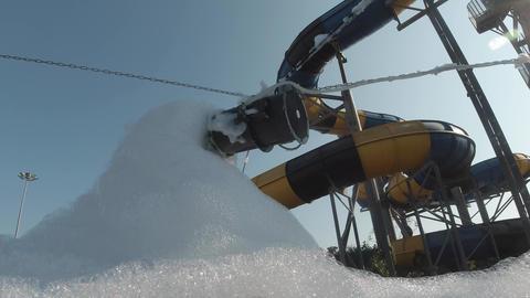 A foam machine against a water slide in a aquapark makes a lot of foam. Foam Live Action