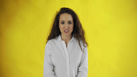 Portrait of a young woman feeling disgust on yellow background Live Action