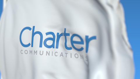 Flying flag with Charter Communications logo, close-up. Editorial loopable 3D Footage
