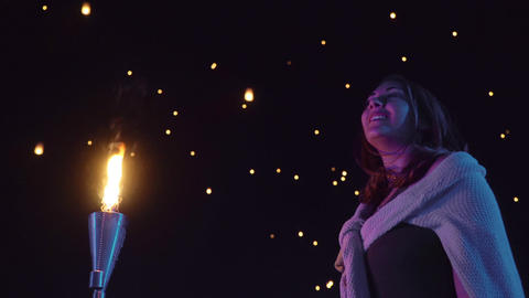 Woman watches as sky lanterns fly Into the night sky Stock Video Footage