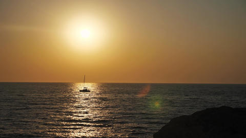 Sunset on the sea with beautiful view of a boat passing on the sun reflection Live Action