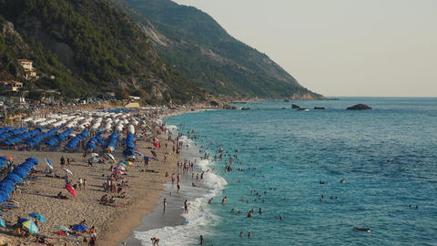 Very beautiful beach with tourists playing into the waves and many umbrellas and sunbeds Live Action