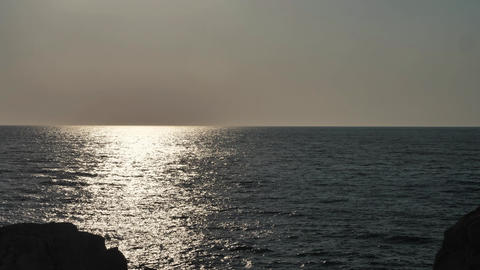 Beautiful sea at dusk with bright sun reflection on the waves Live Action