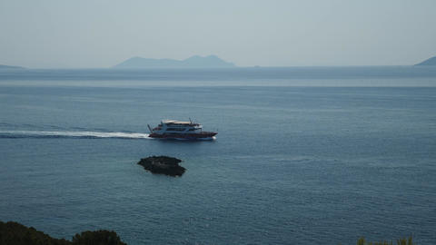 Boat passing on the sea near a big rock Live Action