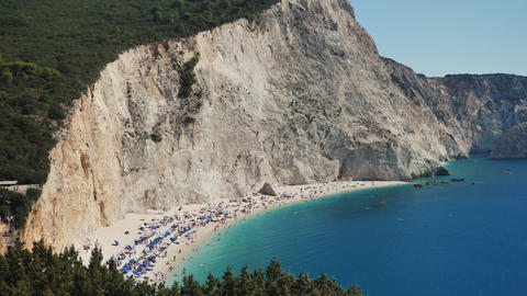 Very beautiful beach with tourists and with blue water near rocky cliffs greece. Perfect shot for Live Action