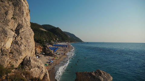 Above view of a very beautiful beach and coast line with tourists playing into the waves and many Live Action