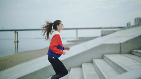 Outdoor shot of fit young woman running up stairs. Female athlete climbing up Live Action