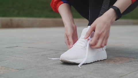 Female Athlete ties up shoelaces, white sneakers, white socks, in sports clothes Live Action