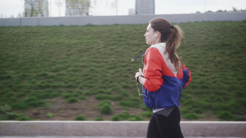 Athletic fitness woman with headphones running in urban city Footage
