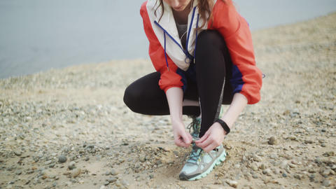 Woman prepare to run runs along the beach by the river. Spory woman tying Footage
