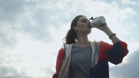 Brunette teenager girl drinking cold water after running in the park. Beautiful Footage