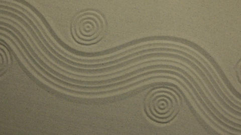 Unusual sand texture. Drawn waves and circles in the sand. With space Live Action