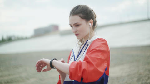 Girl jogging with a smart watch. Woman in headphones with smart watch on sea Live Action